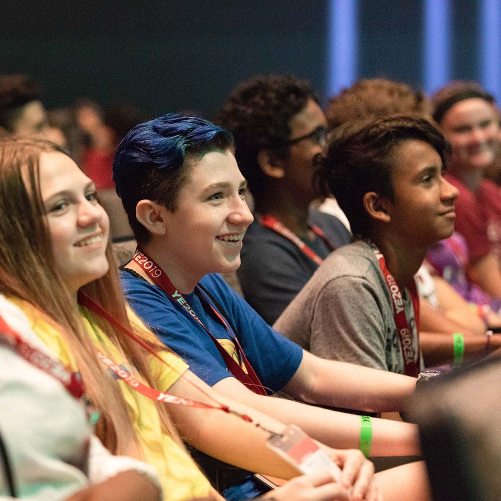 Middle school students seated in an auditorium smiling